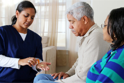 caregiver giving medicine to senior
