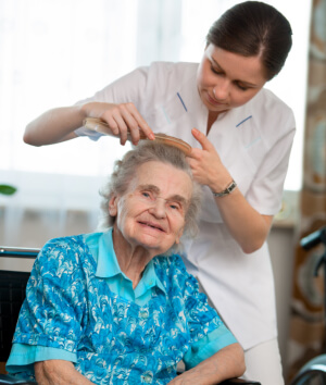 caregiver assisting senior woman in combing her hair